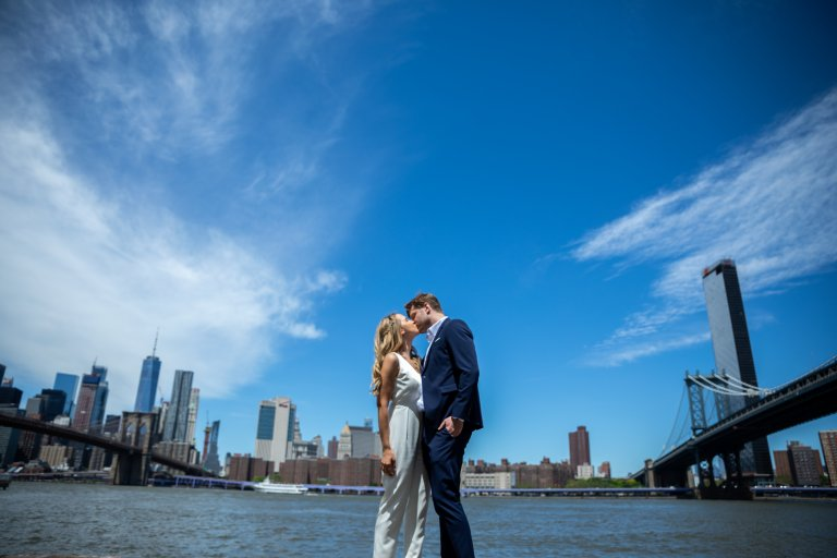 Married couple engagement session dumbo kissing between two bridges New York City